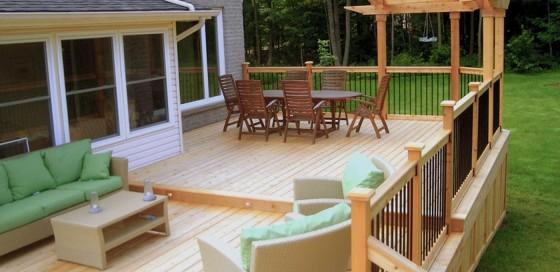 fetching-light-brown-flooring-veranda-green-fabric-cozy-sofa-light-brown-varnished-wooden-table-dark-brown-varnished-wooden-chair-oval-dark-brown-varnished-wooden-table-brown-wooden-flat-roof-backyar