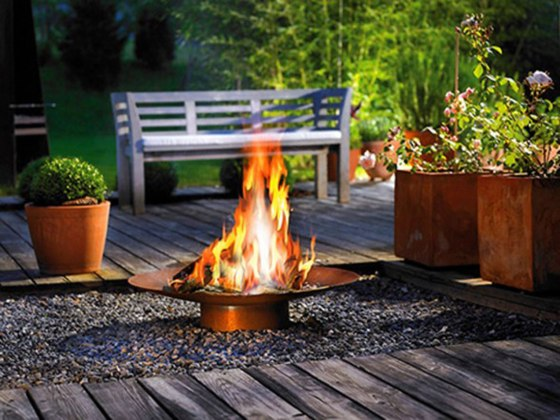 outdoor-copper-fire-bowl-upon-pebbled-ground-with-deck-floor-and-greenery-surround
